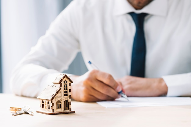 Schlüssel und haus in der nähe vom schreiben des immobilienmaklers Kostenlose Fotos