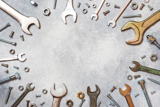 Schlüssel, werkzeugbolzen und nüsse auf grauem konkretem hintergrund mit kopienraum. Premium Fotos