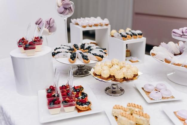 Schmackhafte auswahl an leckeren desserts, kuchen, cupcakes und gebäck auf einem buffettisch bei bankett, party oder hochzeit Premium Fotos