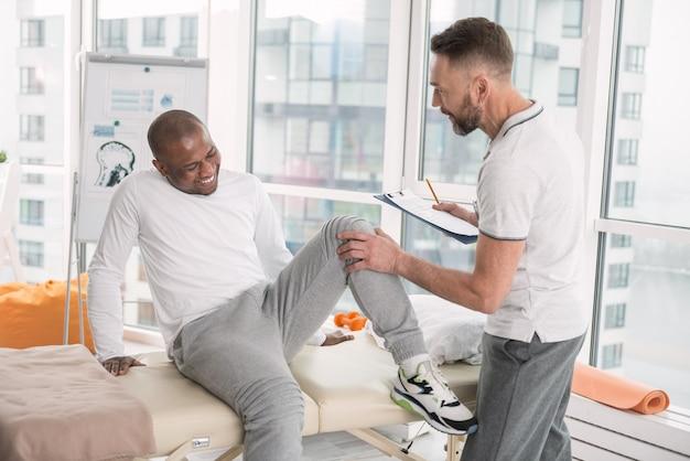Schmerzen im bein. unglücklicher freudloser mann, der unter schmerzen leidet, während er seinen hals beugt Premium Fotos
