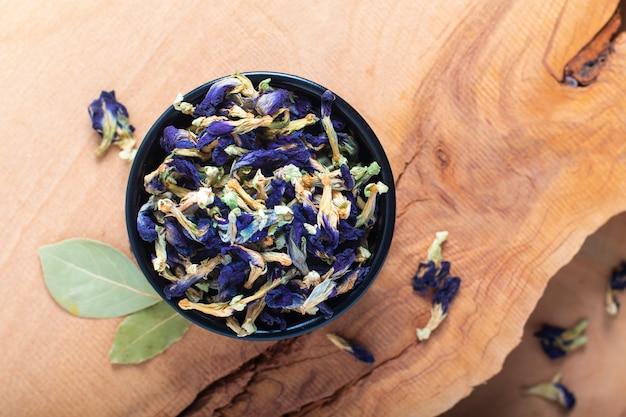 Schmetterlingserbsenblume des lebensmittelkonzeptes trockene für machen den kräutertee in der keramischen schale auf hölzernem brett Premium Fotos