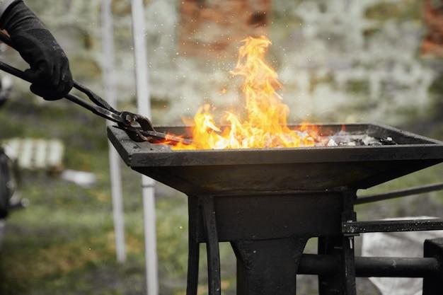 Schmied, der metallstück in brennender kohle erhitzt Premium Fotos