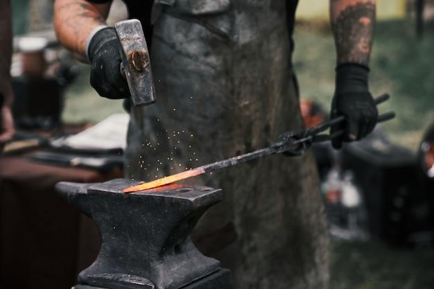 Schmied schmiedet geschmolzenes metall manuell auf amboss Premium Fotos