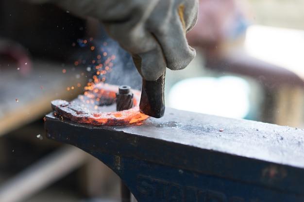 Schmiede, die in der schmiede arbeiten und ein hufeisen machen. Premium Fotos