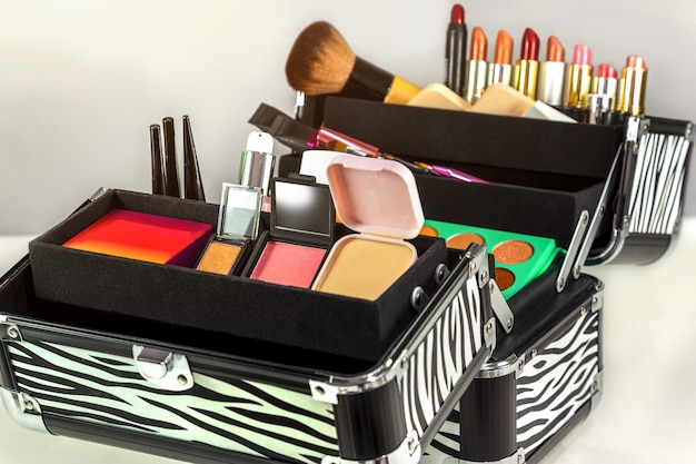 Schminktasche mit bunten lidschatten, lippenstiften, lipglosses, rouges und nagellacken Premium Fotos