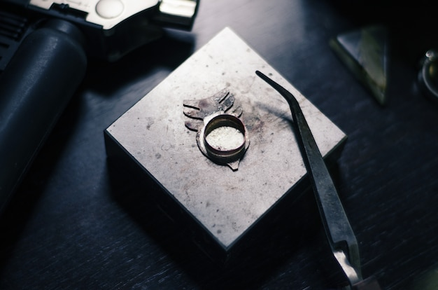 Schmuck aus metall, unvollendet von einem meister auf einem metallständer. juwelierwerkzeuge, brenner und zangen Premium Fotos