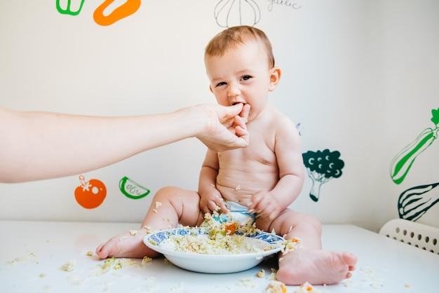 Schmutziges und lächelndes baby auf einer weißen tabelle, die durch die hand seiner mutter eingezogen wird, beim lachen beim versuchen der blw methode. Premium Fotos