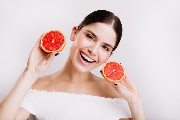 Schnappschuss des jungen grauäugigen mädchens mit schneeweißem lächeln, das saftige und gesunde grapefruits auf weißer wand zeigt. Kostenlose Fotos