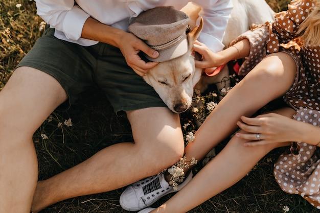 Schnappschuss von mann und frau in sommeroutfits, die labrador retriever mit beiger kappe versehen. Kostenlose Fotos