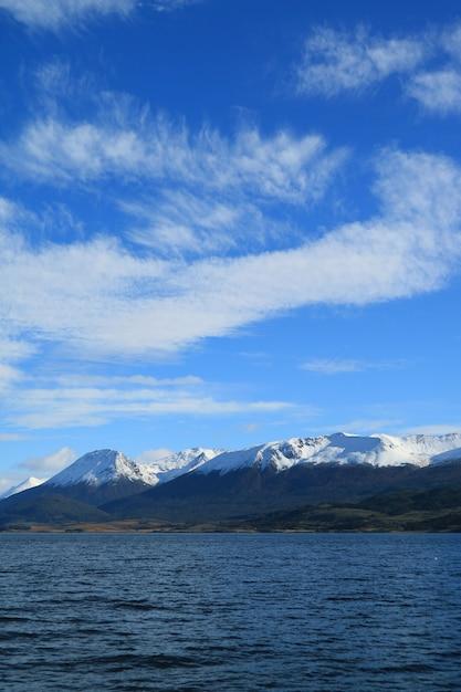 Schnee bedeckte gebirgszugansicht vom kreuzschiff auf spürhundkanal, ushuaia, argentinien mit einer kappe Premium Fotos