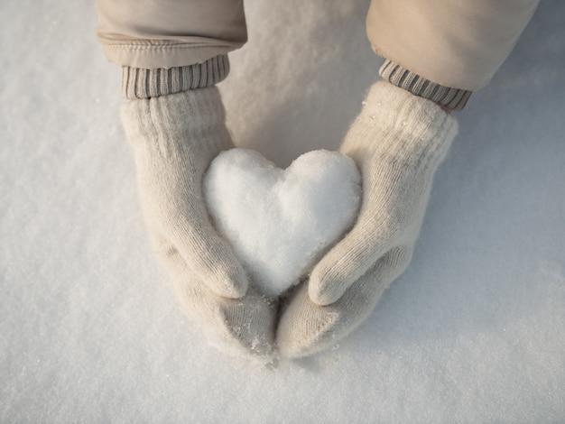 Schnee herz in händen Premium Fotos