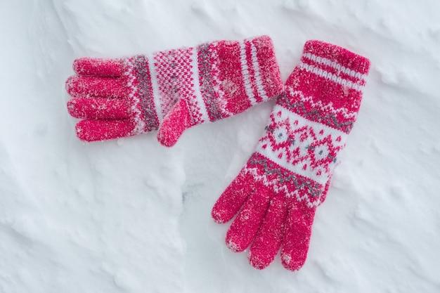 Schneebedeckte handschuhe auf schnee, winterhintergrund. Premium Fotos