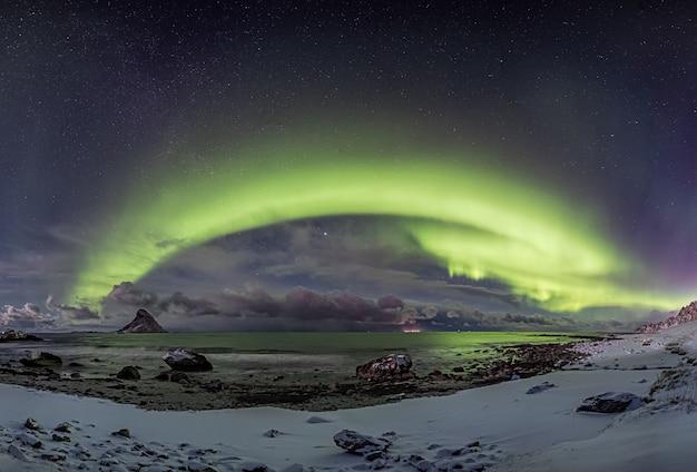 Schneebedeckte küste durch das wasser unter den schönen nordlichtern im sternenhimmel in norwegen Kostenlose Fotos