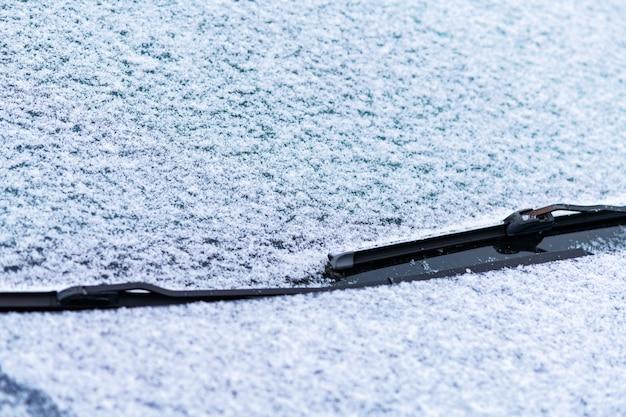Schneebedecktes autofenster mit scheibenwischern Premium Fotos