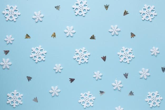 Schneeflocken und weihnachtsbäume auf blauem hintergrund Kostenlose Fotos
