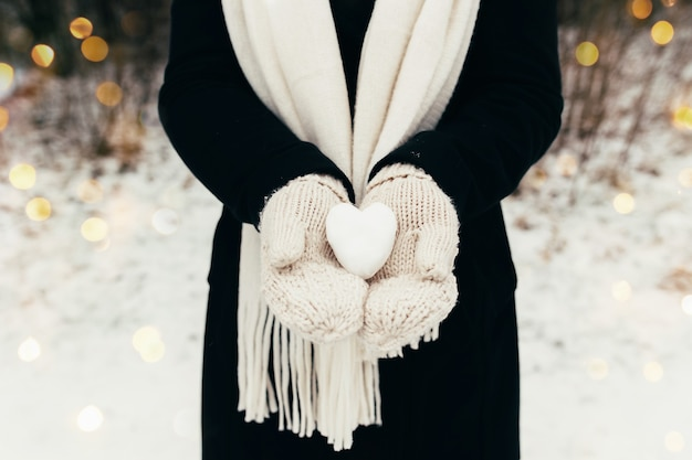Schneeherz schneeball in mädchen behandschuhten händen. unscharfer hintergrund. hochwertiges foto Premium Fotos