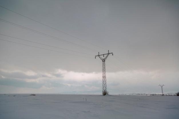 Schneelandschaft des winters mit elektrischen säulen im feld Premium Fotos