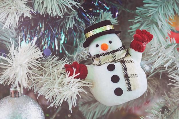 Schneemann auf einem grünen chrismas-baum für festival des neuen jahres Premium Fotos