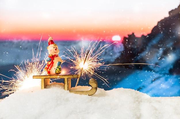 Schneemann auf einem schlitten in einer schneeverwehung vor schneebedeckten bergen Premium Fotos