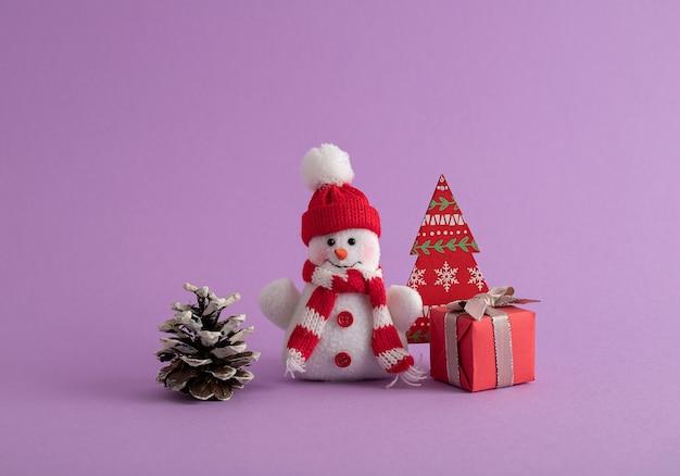 Schneemann, rote geschenkbox, tannenzapfen und ein weihnachtsbaum aus papier im lila raum Kostenlose Fotos
