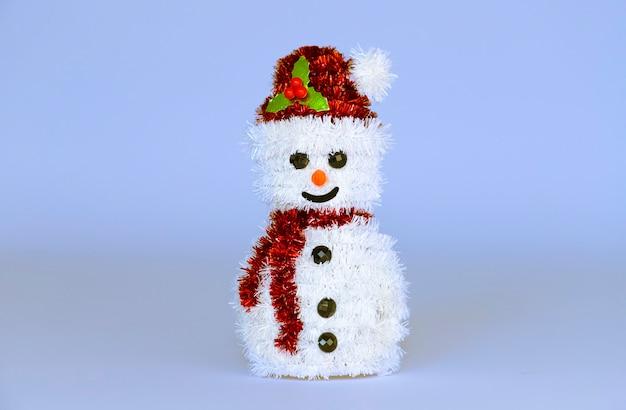 Schneemannspielzeug auf einem eisblauen kopierraumhintergrund. Premium Fotos