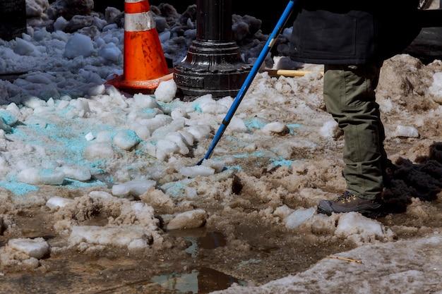 Schneeräumung im hof. mann in einer jacke und stiefeln Premium Fotos
