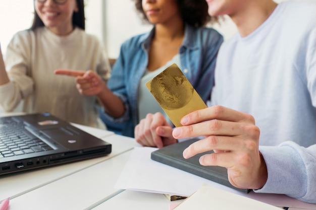 Schneiden sie ansicht eines kerls, der eine kreditkarte in seinen händen hält, während er laptop mit mädchen zusammen betrachtet. Premium Fotos