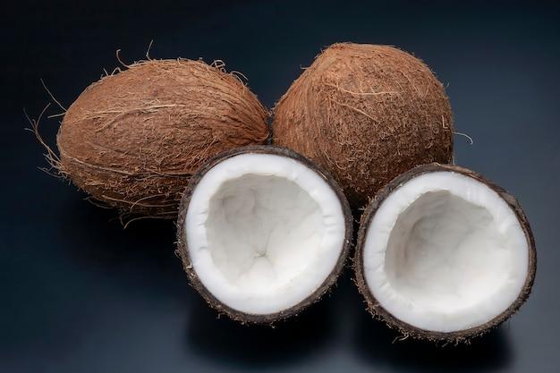 Schneiden sie frische kokosnuss auf einem dunklen hintergrund. vitaminfrüchte. gesundes essen Premium Fotos