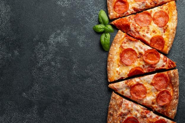 Schneiden sie in scheiben leckere frische pizza mit peperoni Premium Fotos