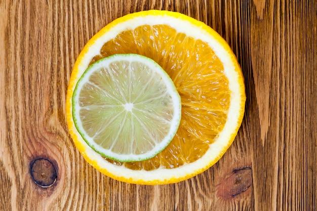 Schneiden sie nebeneinander liegende orangen- und limettenscheiben und fotografieren sie sie in nahaufnahme. kleine schärfentiefe Premium Fotos