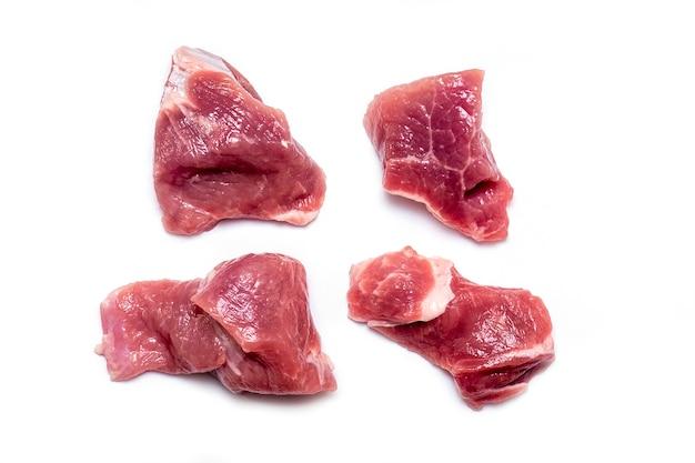 Schneiden sie stücke schweinefleisch des rohen fleisches, das rindfleisch, das auf weißem hintergrund lokalisiert wird Premium Fotos
