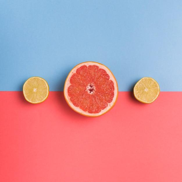 Schneiden sie zitrusfrüchte auf buntem hintergrund Kostenlose Fotos