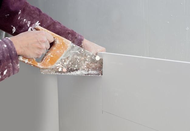 Schneiden von gipskarton gips hand schmutzig sah Premium Fotos