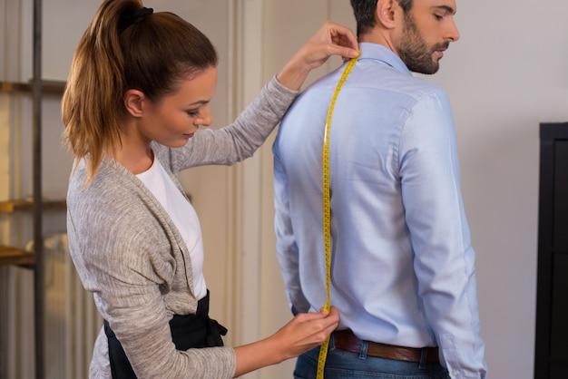 Schneider, der nahe männlichem klienten steht, der zurück misst. schneiderfrau, die maßnahmen für neues geschäftshemd unter verwendung des bandmessers ergreift. junger modedesigner, der maß des mannes trägt, der hemd im laden trägt. Premium Fotos