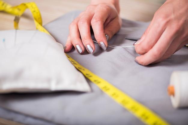 Schneiderhände, die an neuer kleidung arbeiten Premium Fotos