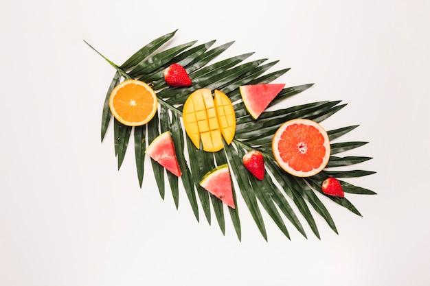 Schneidet appetitanregende rote wassermelonenerdbeerorange mango am palmblatt Kostenlose Fotos