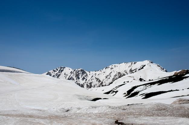 Schneien sie auf bergen und ansicht des blauen himmels an murodo-station alpinen weges tateyama kurobe, japan-alpen Premium Fotos