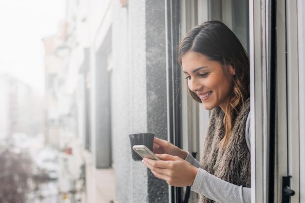 Schnelle nachricht an einen freund. nette moderne frau, die intelligentes telefon hält. Premium Fotos