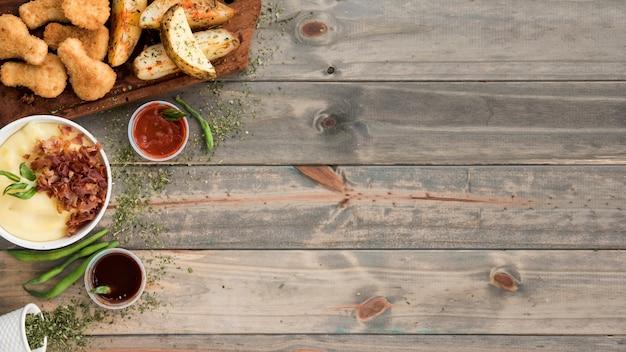 Schnellimbiß der kartoffel und des huhns auf hölzernem schreibtisch Kostenlose Fotos