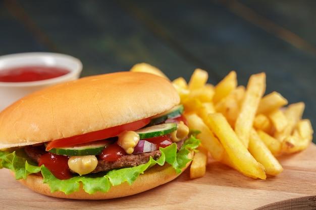 Schnellimbiß, selbst gemachter burger auf einem hölzernen hintergrund Premium Fotos