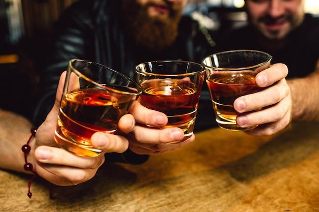 Schnittansicht von drei bärtigen jungen männern, die gläser mit rum zusammenhalten. sie lächeln. die leute sitzen in der bar. Premium Fotos
