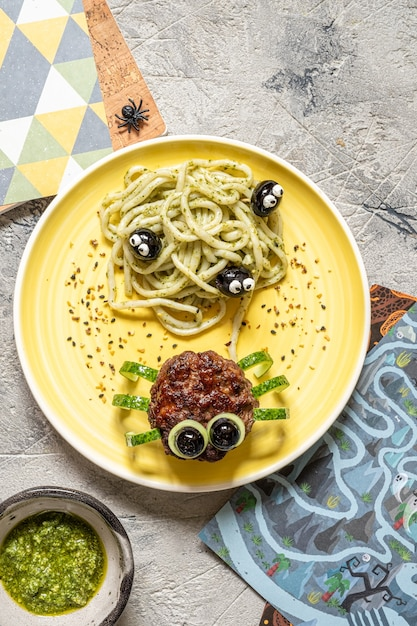 Schnitzel sehen aus wie eine spinne mit pesto-nudeln für halloween Premium Fotos
