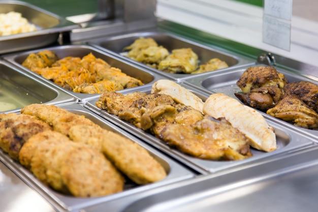 Schnitzel und fleischgerichte in buffetform auf metallplatten. selektiver fokus Premium Fotos