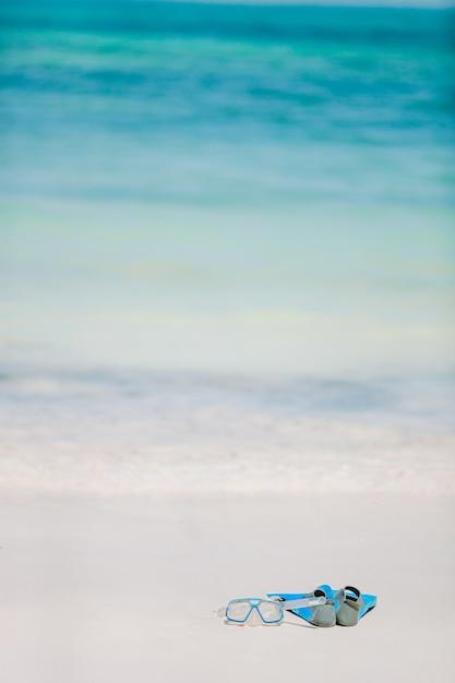 Schnorchelausrüstung maske, schnorchel und flossen am weißen strand Premium Fotos
