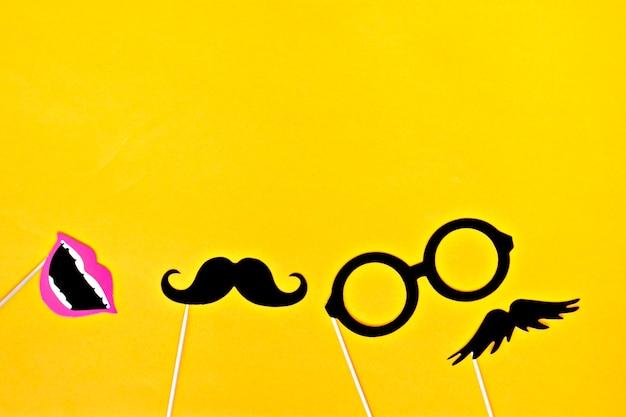 Schnurrbart, krawatte, gläser, roter mund auf hölzernen stöcken gegen hellen gelben hintergrund flach Premium Fotos
