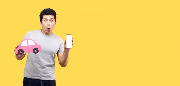 Schock und überraschungsgesicht des asiatischen mannes, der papierautoform hält, das smartphone lokalisiert auf gelber wand hält Premium Fotos