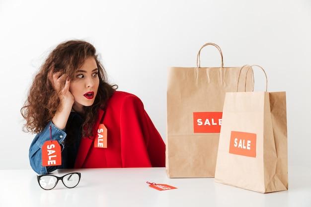 Schockierte einkaufsverkaufsfrau, die mit papiereinkaufstüten sitzt Kostenlose Fotos