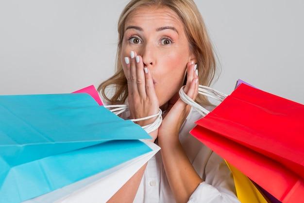 Schockierte frau, die mit vielen bunten einkaufstaschen aufwirft Kostenlose Fotos