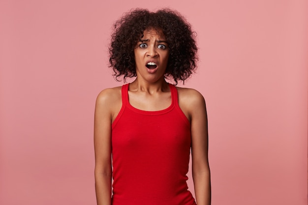 Schockierte junge dunkelhäutige dame mit kurzen braunen lockigen haaren, die ein rotes hemd tragen, die hände am körper halten und mit schmollmund schauen, augen mit weit geöffnetem mund abrunden Kostenlose Fotos