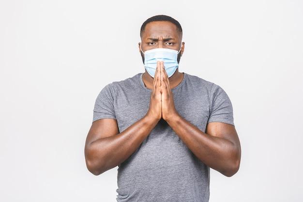 Schockierter afroamerikanermann, der hygienemaske trägt, um infektion, luftgetragene atemwegserkrankung zu verhindern Premium Fotos